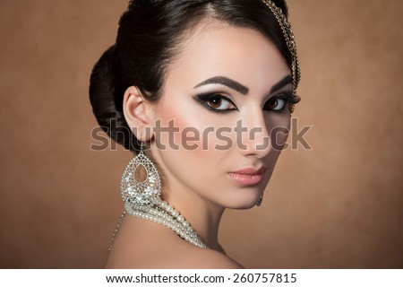 Portrait of young beautiful asian woman with evening make-up over beige background - stock photo