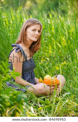 Portrait of young beautiful attractive blond woman sitting in grass and holding basket with ripe fruits at summer green park.