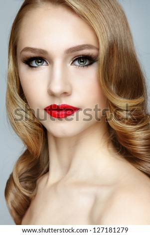 Portrait of young beautiful blond girl with red lipstick and stylish hairdo - stock photo