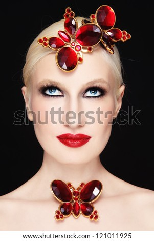 Portrait of young beautiful blond girl with stylish make-up and red plastic butterflies - stock photo