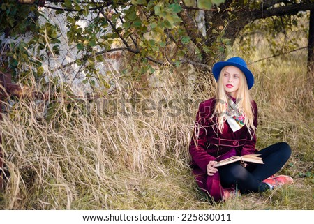portrait of young beautiful blond hipster woman reading paper book on sunny autumn day outdoors copy space background - stock photo
