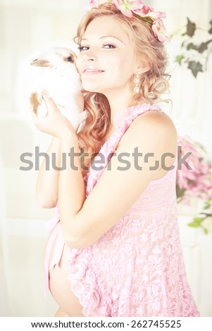 Portrait of young beautiful blond pregnant woman wearing in pink with white rabbit and pink flowers on her head. with long curly hair. - stock photo