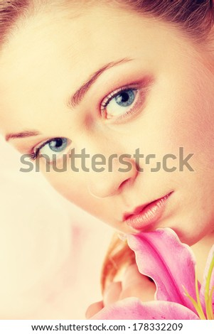 Portrait of young beautiful blond woman with lily flower - stock photo