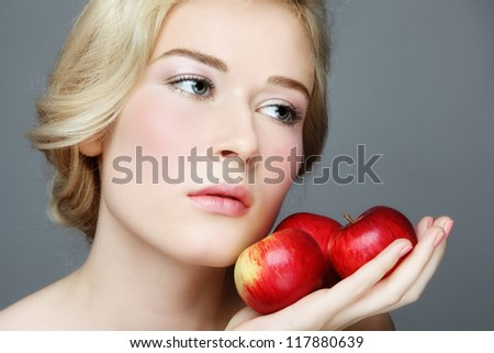 Portrait of young beautiful blond woman with red apples in her hands