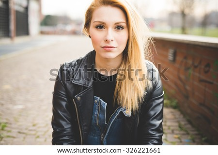 Portrait of young beautiful blonde straight hair woman in the city, looking in camera, pensive - wearing a black leather jacket - carefreeness, youth concept - stock photo