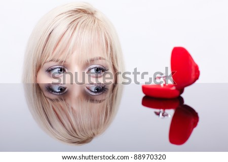 portrait of young beautiful blonde woman behind mirror table looking at red ring box - stock photo