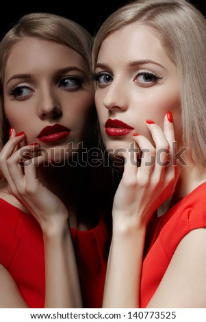 portrait of young beautiful blonde woman in red dress posing at mirror and touching her face with manicured fingers