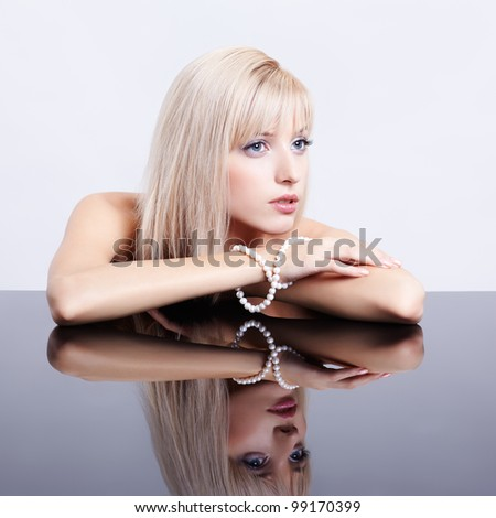 portrait of young beautiful blonde woman sitting with string of pearls at reflecting table - stock photo
