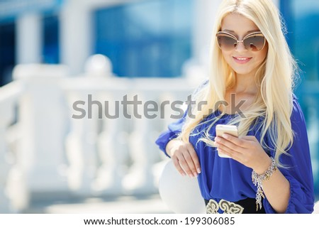 Portrait of young beautiful blonde woman using cellphone outdoors in the city