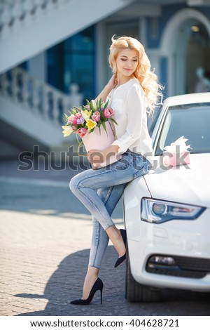 portrait of young beautiful blonde woman with box of flowers by car. flower box and gift box. spring time outdoor photo. bouquet of flowers in gift box. birthday, March 8, Valentine's Day, romantic - stock photo
