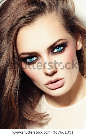 Portrait of young beautiful blue-eyed woman with smoky eyes - stock photo
