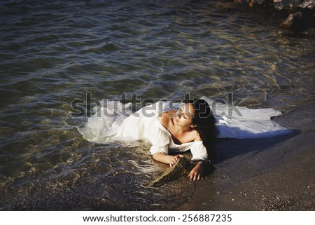 Portrait of young beautiful bride outdoors near sea - stock photo