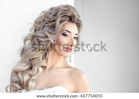 Portrait of young beautiful bride over white background. Make-up and hairstyle for the wedding. - stock photo