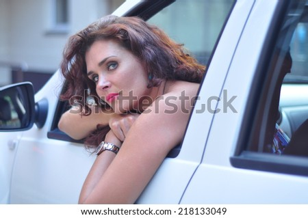 Portrait of young beautiful brunette Caucasian woman in her white car looking bored. Traffic jam concept, negative human emotion concept. - stock photo