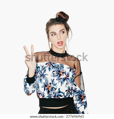Portrait of young beautiful brunette girl posing for camera inside. Bright makeup, hairdo and casual style. White background, not isolated. - stock photo