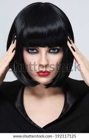 Portrait of young beautiful brunette touching her black hair - stock photo