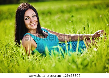 Portrait of young beautiful brunette woman blue bright dress, laying on grass at summer - stock photo