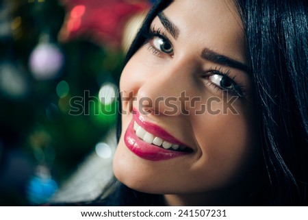portrait of young beautiful brunette woman happy smiling & looking at camera on Christmas tree background - stock photo