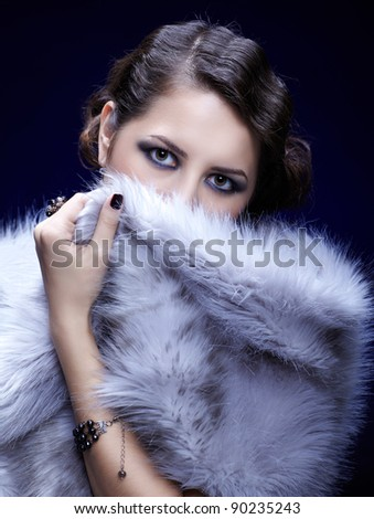 portrait of young beautiful brunette woman hiding lower part of her face in fur mantlet