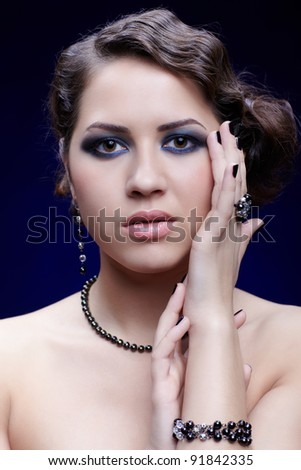 portrait of young beautiful brunette woman in beads, ring abd bracelet - stock photo