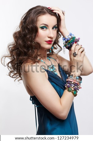 portrait of young beautiful brunette woman in blue dress, in beads, rings, ear-rings and bracelets on gray