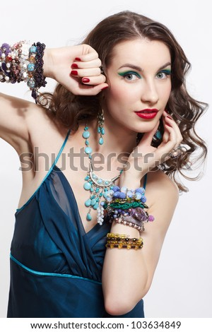 portrait of young beautiful brunette woman in blue dress in in rings, bracelets, ear-rings and beads posing on gray