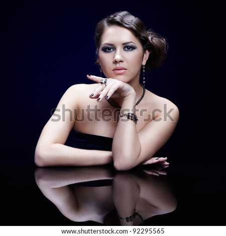 portrait of young beautiful brunette woman in bracelet, beads, ring and ear-rings at mirror table on blue - stock photo