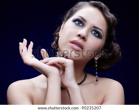 portrait of young beautiful brunette woman in ear-rings and beads - stock photo
