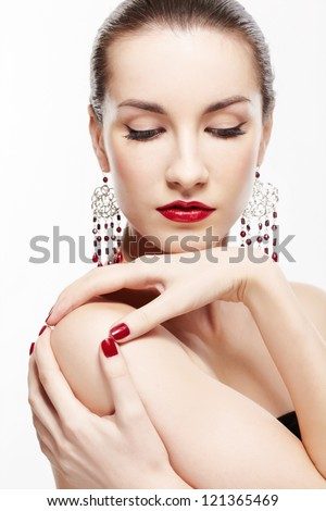 portrait of young beautiful brunette woman in ear-rings touching her shoulder with manicured hands - stock photo