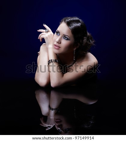 portrait of young beautiful brunette woman in in bracelet, beads, ring and ear-rings at mirror table - stock photo