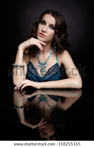 portrait of young beautiful brunette woman in jewelery at mirror table - stock photo