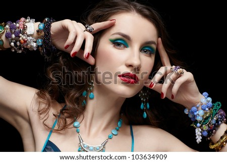 portrait of young beautiful brunette woman in jewelery on black - stock photo
