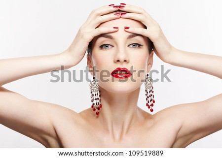 portrait of young beautiful brunette woman in jewelery posing on gray with manicured hands over head - stock photo