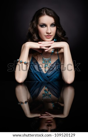 portrait of young beautiful brunette woman in jewelery sitting at reflecting table - stock photo