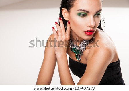 portrait of young beautiful brunette woman in jewellery sitting over white background - stock photo