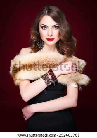 Portrait of young beautiful brunette woman in jewelry and fur standing over red background. Vogue style. Studio shot. Perfect hair and skin. - stock photo