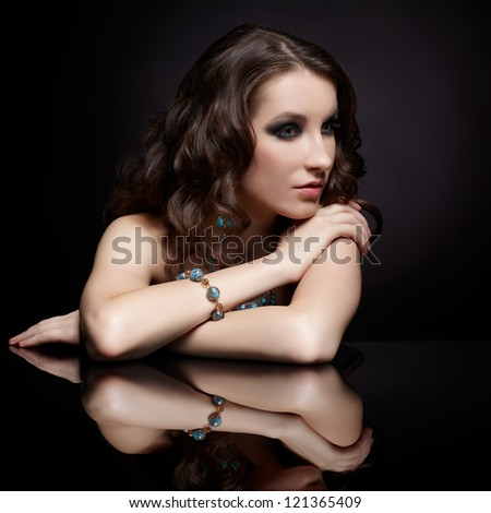 portrait of young beautiful brunette woman in jewelry at black reflecting table - stock photo