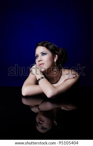 portrait of young beautiful brunette woman in jewelry at mirror table on blue - stock photo