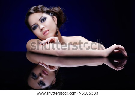 portrait of young beautiful brunette woman in jewelry at reflecting table - stock photo