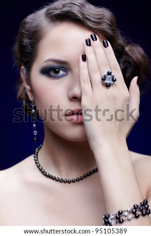 portrait of young beautiful brunette woman in jewelry closing half of face with hand with manicured fingers and fancy ring - stock photo