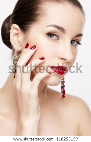 portrait of young beautiful brunette woman in jewelry touching her cheek with manicured hand - stock photo