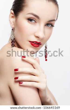 portrait of young beautiful brunette woman in jewelry touching her shoulder with manicured hand - stock photo