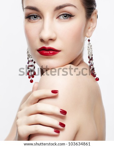 portrait of young beautiful brunette woman in jewelry touching shoulder with manicured fingers - stock photo