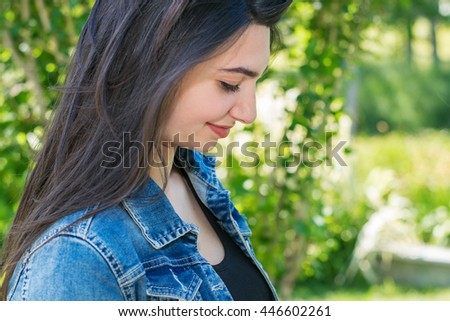 portrait of young beautiful brunette woman in summer Park