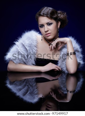 portrait of young beautiful brunette woman in tippet and jewelery at mirror table - stock photo