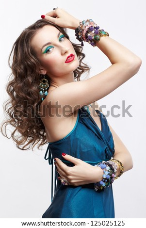 portrait of young beautiful brunette woman posing in blue dress and jewelery on gray - stock photo
