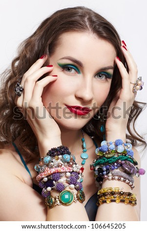 portrait of young beautiful brunette woman posing in blue dress, in beads, rings, ear-rings and bracelets on gray - stock photo