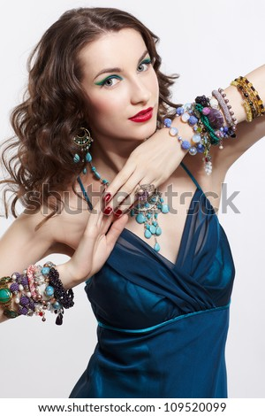 portrait of young beautiful brunette woman posing in blue dress in in rings, bracelets, ear-rings and beads on gray