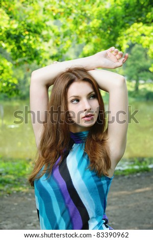 Portrait of young beautiful brunette woman wearing blue blouse and holding arms up at summer green park.