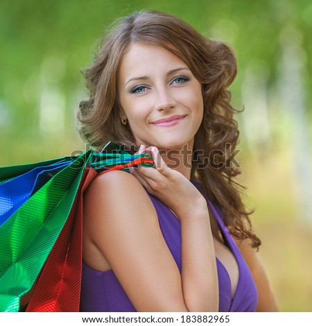 Portrait of young beautiful brunette woman wearing violet top and holding many bags at summer green park. - stock photo